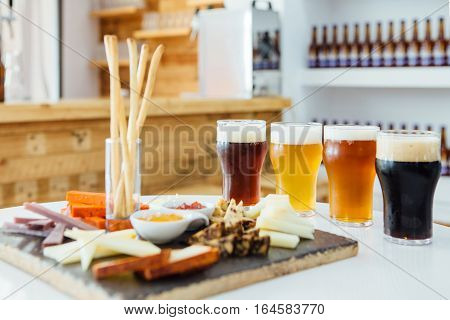 View on table with snack board and four glasses of different craft beer