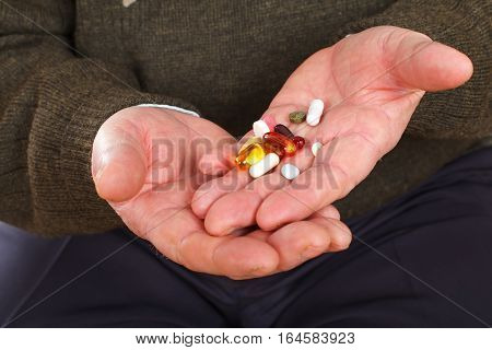 Close up picture on an elderly man holding his pills