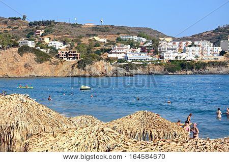 BALI, CRETE - SEPTEMBER 16, 2016 - Tourists relaxing on Livadi Beach with thatched parasols in the foreground Bali Crete Greece Europe, September 16, 2016.