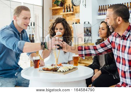 Four adult people tasting craft beer at table with snacks