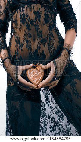 Female hands in black lace gloves hold heart shaped gingerbread cookie with red ribbon against black transparent lace dress legs in stockings incognito close up. Valentine's day and love concept