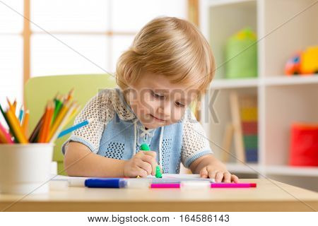 Little boy paints in his nursery at home
