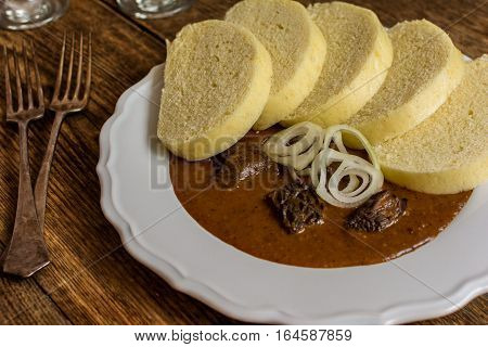 Homemade beef goulash with dumplins and onion on wood table