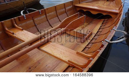 Close-up of wooden rowing boat with oars stowed