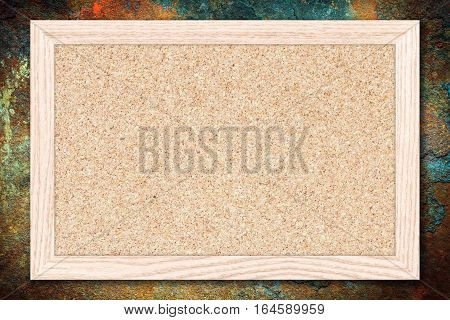 Cork board or Empty bulletin board with a wooden frame on rusty metal background with copy space for text or image.