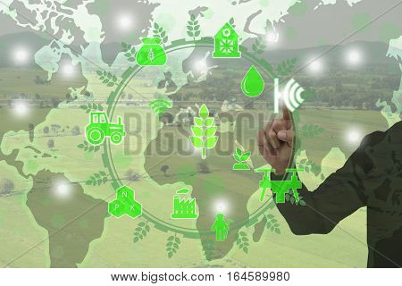Internet of things(agriculture concept)smart farmingindustrial agriculture.Farmer point hand to use augmented reality technology to control monitor management in the farmcredit world map by nasa