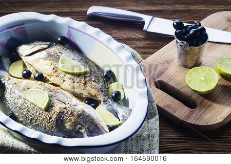 Fresh uncooked dorado with lemon lime olives oil and spices on rustic wooden board. Raw fresh fish with seasonings in roasting pan before baking on brown wooden background.
