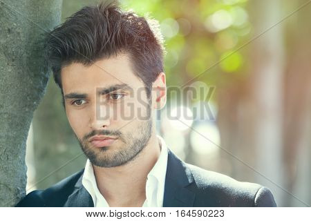 Anxiety and thoughts of young and handsome man. A beautiful and sensual man is thoughtful, near a tree. Gaze, beard and stylish hair.