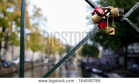 Amsterdam canal, Holland, Netherlands - view from bridge, wedding locks, close up