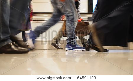 People walking on moving staircase with luggage in the international airport, close up shot of legs and shoes, Istanbul, Ataturk