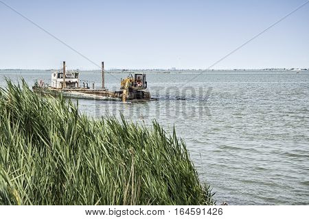 Man on dredger at work in the delta of the river Po on July 07 2016 in Porto Tolle, Rovigo, Italy
