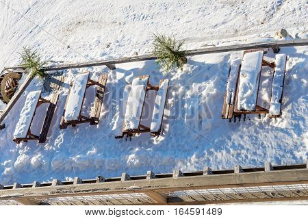 Wooden tables outdoors with snow on patio of mountain cabin on sunny winter day