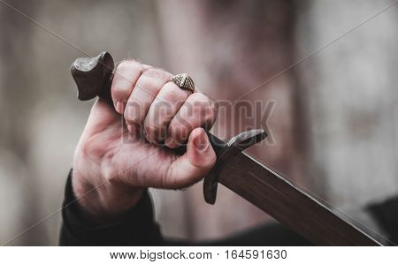 antique sword in the man's hand close-up