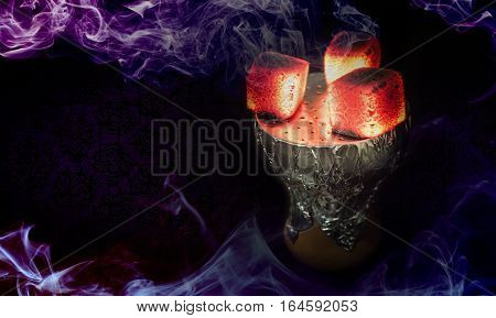 Hookah hot coals for smoking shisha and leisure in east pattern background. Bowl with tobacco and coal.