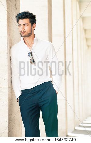 Handsome and stylish young man. Hair and beard fashionable. A beautiful young Italian man is outdoors. He is leaning against a marble wall. He wears a white shirt and dark trousers. Sunglasses. Behind him, on endless background, an ancient marble building
