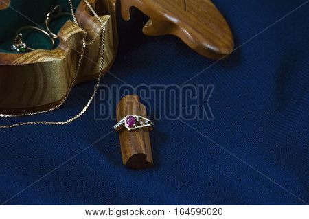 One golden ring and chain near the wooden box on the deep blue background