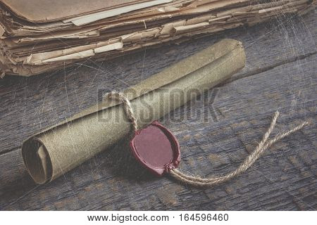 Old manuscript and a pile of old paper lying on the wooden table.The stylized photo