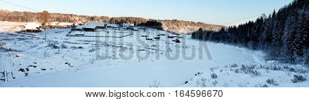 Winter in Russian village. Panorama of Russian heartland. Winter sunset in the Russian province. Snowy field. Frozen river