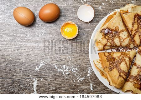 Hotcakes with syrup on plate on wooden table