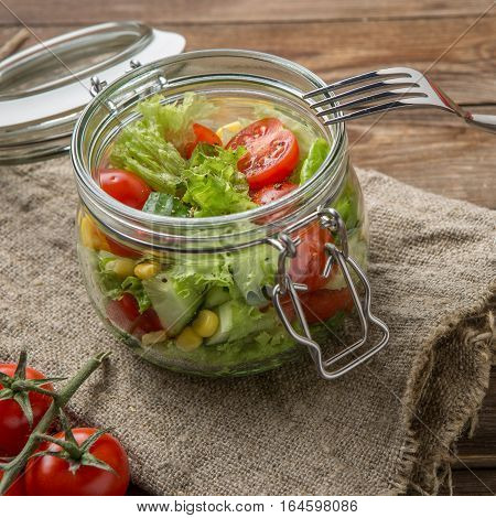 Vegetable salad in beautiful pot on table with linen napkin