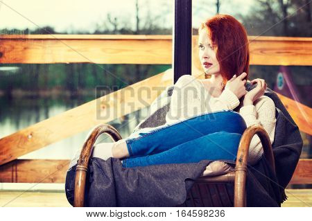 Atractive Red-haired Woman Resting Sitting On Rocking Chair In F