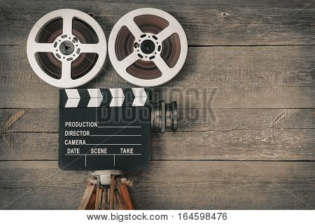 Old movie camera consisting of a tripod lens film reels and clapperboards
