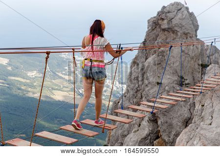 Brunette walking on rope ladder with insurance among mountain scenery