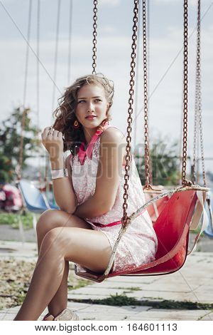 beautiful young blonde girl enjoying the summer in the Park of old rides and carousels.