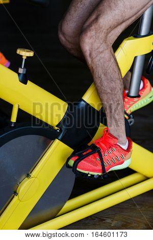 Athlete training on stationary bike at sports center