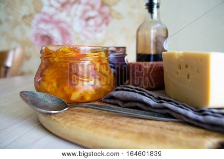 Big piece of cheese salami and jar with jam. Wooden cutting board.