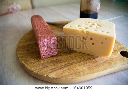 Big piece of cheese and salami. Wooden cutting board. Minimalistic picture.