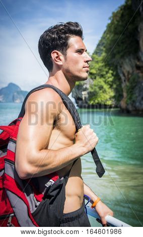 Portrait of young handsome bare chested brunet man looking away against seascape on a boat or ship, with rucksack on shoulder