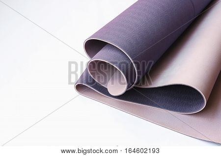 Yogi essentials. Lilac yoga mat on white background with copy space. Yoga practice concept.