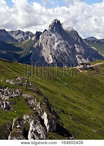 mountain meadow and Rifugio Sass Bece on Padon mountain ridge with Colac mountain peak on the background above Passo Pordoi in Dolomites in Italy