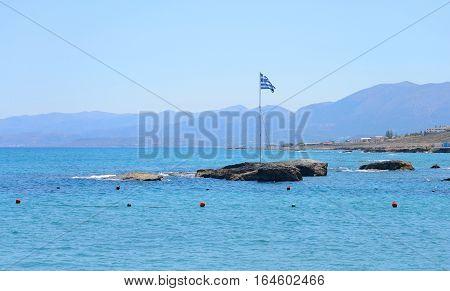 Rocks on the coast of Cretan Sea the flagpole with the Greek flag near Hersonissos Crete Greece.