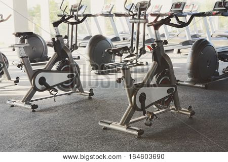Modern gym interior with equipment. Fitness club with row of training exercise bikes, backlight. Healthy lifestyle concept
