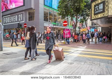 Hong Kong, China - December 6, 2016: A tourist with trolley and Apple phone at Yee Wo street junction. Causaway Bay is one of the best and the busiest shopping downtown.
