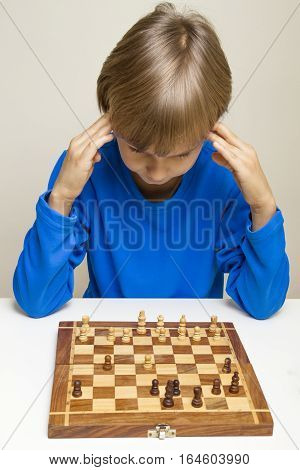 Serious chess player kid looking at chess board and thinking about the next move