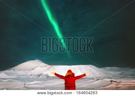 Traveler enjoying Northern lights view above mountains raised hands Travel Lifestyle and success concept vacations into the wild night scene