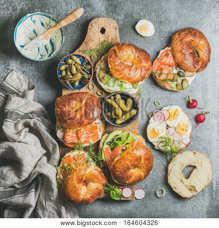Variety of bagels with smoked salmon, eggs, radish, avocado, cucumber, greens and cream cheese in bowl for breakfast, lunch, party or takeaway on wooden board over grey concrete background, top view