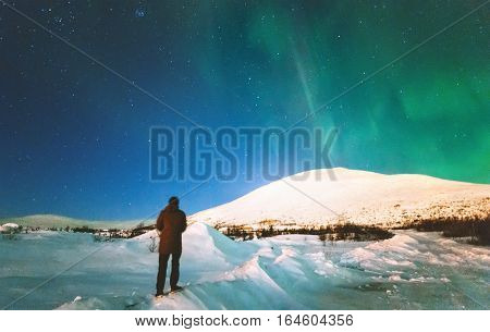 Traveler man enjoying Northern lights view above mountains Travel Lifestyle emotional concept vacations into the wild night scene
