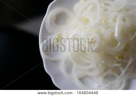 Sliced onion rings on white plate standing on glass transparent table with copy space