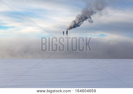 smoke pipes in heavy fog in winter on a background cloudy sky