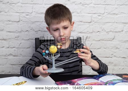 Cute little boy is playing with the model of the planetary system, opened book on the desk, white brick wall behind