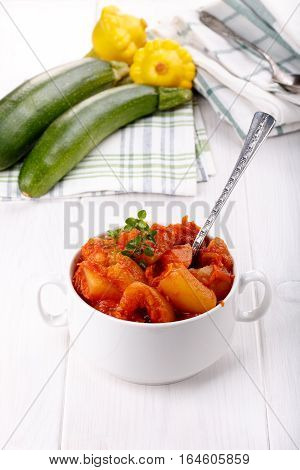 Vegetable stew in white bowl. Vegetable ragout of zucchini squash onions carrots and tomatoes.
