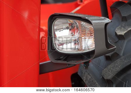 Headlight on the new red tractor. Close up.