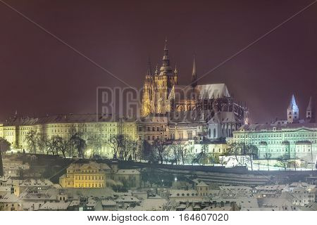 Night winter Prague Castle the Castle and St. Vitus Cathedral. Snowy roofs of the old town in the background Prague Castle. Czech Republic.