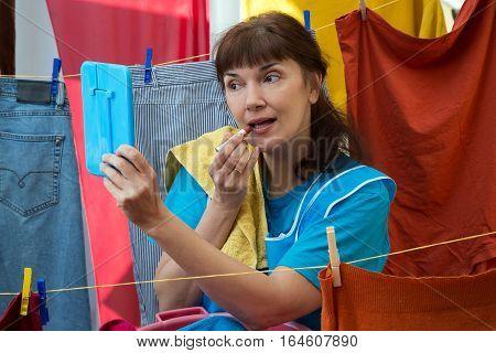Woman hanging up linen and doing makeup