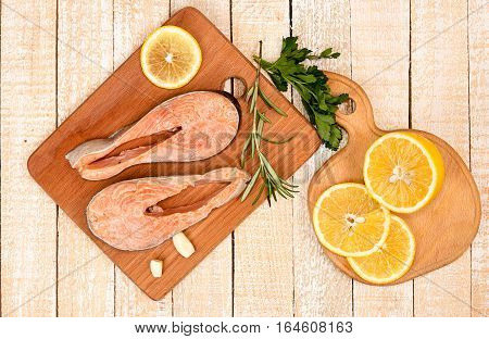 Raw marinated trout fillet on wooden cutting board. Steak of trout ready to frying. Wooden background. Top view. View from above. Healthy delisious food concept.