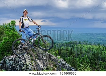 Oldman-Stone peak, Russia - July 28, 2007: Biker tourist in final point of a route. Around the dry tumbled-down trees. Height is 755 m. Sverdlovskaya region near Leviha